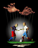 Rigged sports. Wooden puppets as football (soccer) players, manipulated by the fingers of two big hands to play as somebody wants Stock Photos