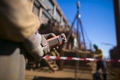 Мужская рука rigger контролируя нагрузку красного крана подъема удаленную поднимаясь пока расплывчатое изображение его помощи дру стоковые фото