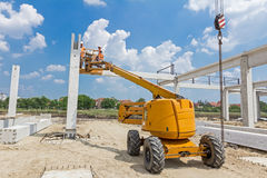 Rigger is in the cherry picker on construction site Stock Photo