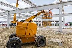Rigger is in the cherry picker on construction site Royalty Free Stock Images