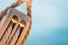 Rigging, maritime scene, close-up of wooden pulley with nautical ropes. Yachting, nautical pulley with ropes of a classical sailing boat and blured blue sea royalty free stock photo