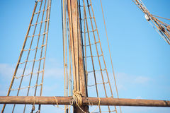 Rigging and ropes of ancient sailing boat. Detail of mast of old antique historic wooden sailing ship, with rigging and ropes, blue sky and copy space Stock Photography