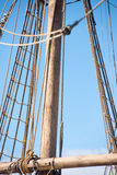 Rigging and ropes of old timber sailing boat. Detail of mast of old historic wooden sailing vessel, with rigging and ropes, blue sky and copy space Royalty Free Stock Photos