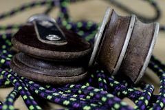 Rigging, sailing accessories. Rope block and shekel on a wooden. Table. Black background Royalty Free Stock Photo