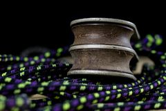 Rigging, sailing accessories. Rope block and shekel on a wooden. Table. Black background Royalty Free Stock Image