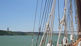 Rigging of sailing ship on background of 25th April bridge and statue of Jesus stock footage