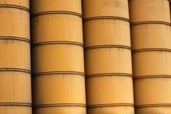 Righe dei barilotti industriali gialli enormi Immagine Stock