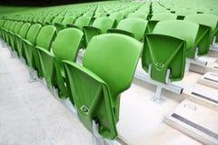 Righe delle sedi piegate e verdi in stadio vuoto. Fotografia Stock