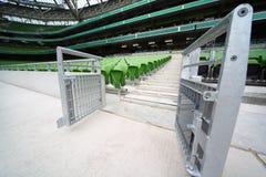 Righe delle sedi piegate e verdi in stadio vuoto Immagini Stock