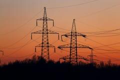 Righe di trasmissione di energia elettrica al tramonto Fotografie Stock