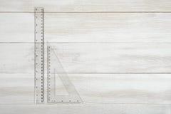 Righello di plastica del diritto-bordo e triangolare sulla tavola di legno Fotografie Stock