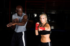 Right Cross. Beautiful but dangerous female fighter working on her right cross with her trainer in an Mixed Martial Arts gym Stock Image