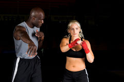 Right Cross. Beautiful but dangerous woman fighter practicing her right cross with her trainer in an Mixed Martial Arts gym Stock Photography