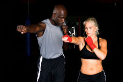 Right Cross. Beautiful but dangerous woman fighter working on her right cross with her trainer in an Mixed Martial Arts gym Stock Photos