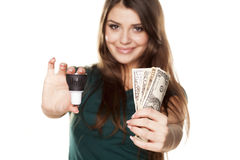 The right decision. Smiling girl shows how you can save money with LED bulb stock image