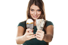The right decision. Smiling girl shows how you can save money with LED bulb Stock Photo