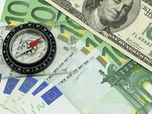 Right direction. Money background (euros and dollars) with compas showing in dollars direction Stock Images