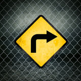 Right Direction Grunge Yellow Warning Sign on Chainlink Fence Royalty Free Stock Photography