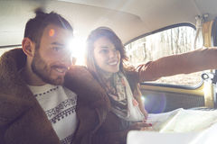 Right direction. Young couple having fun and enjoying a road trip both sitting at the back seat of a car and reading the map in search of the right direction stock images