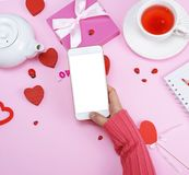 Right female hand in a pink sweater is holding a white smartphon Stock Photo