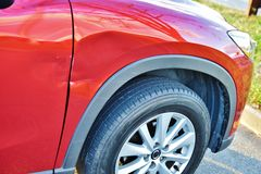 Right fender dent mazda cx-5 car door scrach. There is right fender dent and scratch on the door of Mazda Cx-5 Sport car , not so large damage , but needs time Stock Photography