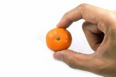 Right hand holding fresh orange. Right hand holding orange on isolated background Stock Photo