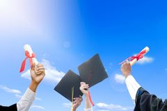 The right hand holds degrees in to sky. There is a hat throw in the sky. Show the success of education. photo concept education and Success royalty free stock image
