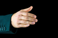 The right hand of a man, ready for a handshake. Close-up of the right hand of a man, wearing black business suit, ready for a handshake, symbol of agreement or Stock Photo