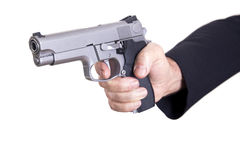 Aiming the Gun. The right hand of a mature adult man wearing a suit, holding a 9mm gun with both hands aiming it to the target Royalty Free Stock Image