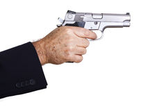 Aiming Loaded Gun - Close Up. The right hand of a mature adult man wearing a suit, holding a 9mm gun with both hands aiming it to the target Royalty Free Stock Photos