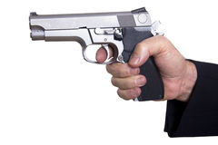 Aiming Loaded Gun - Close Up. The right hand of a mature adult man wearing a suit, holding a 9mm gun with both hands aiming it to the target Stock Photo