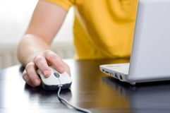 Right hand on the mouse. Man in yellow shirt with his right hand on the mouse (shallow DOF Royalty Free Stock Photo