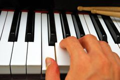 Right hand playing on piano keyboard Stock Photos