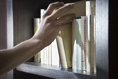 Right hand reaching for a book. Right hand of a young man picking a book in a wooden shelf royalty free stock photo