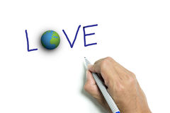 Right hand writing 'LOVE' and the earth Stock Images