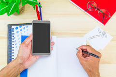 Right hand writing on notebook and left hand holding smartphone on wooden desk with office supplies, glasses and green leaves pot Royalty Free Stock Photos
