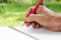 Right hand writing with red pencil Royalty Free Stock Images