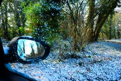 In The right hand corner a car wing mirror reflecting the snow s. In the right of the image an out of focus car wing mirror reflecting the snow scene, in the Stock Photo
