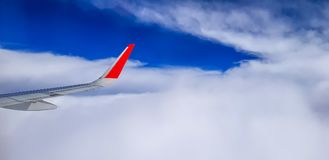 Right jet plane wing over the cloudy sky. Right jet plane wing with red wingtip over the cloudy sky Royalty Free Stock Image