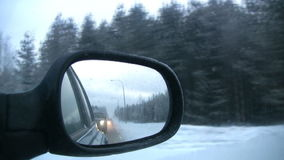 Right mirror of the car. Kind on a snow-covered pine wood in the right mirror of the moving car. Twilight. Finland stock video footage