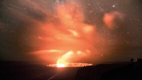 Right moving time lapse video of Milky Way moving, falling stars and cloud layer over the plain with fire burning in the