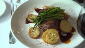 Right pan of a fillet mignon meal with red wine stock video