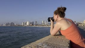 Pan to a female tourist photographing Tel Aviv. Right pan to a female tourist photographing Tel Aviv stock video footage