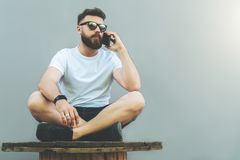In right part of image young attractive bearded hipster man in sunglasses and white T-shirt. Is sitting cross-legged and talking on his cell phone.Man resting Royalty Free Stock Photo