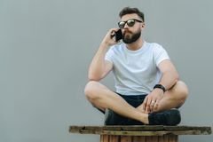 In right part of image young attractive bearded hipster man in sunglasses and white T-shirt is sitting cross-legged. And talking on his cell phone.Man resting Stock Images