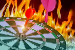 Dart hitting on center with fire on dartboard for business concept. Right on target concept using dart in the bulls eye on dartboard business success concept stock images