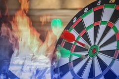 Dart hitting on center with fire on dartboard for business concept. Right on target concept using dart in the bulls eye on dartboard business success concept stock photo