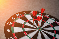 Right on target concept using dart in the bullseye on dartboard Stock Photos