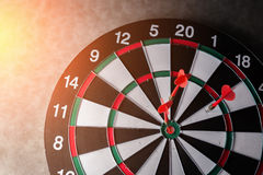 Right on target concept using dart in the bullseye on dartboard Stock Images