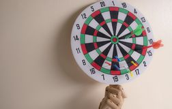 Red dart on the dartboard over the wooden hand. Right on target concept using dart in the bullseye on dartboard business success concept royalty free stock photo